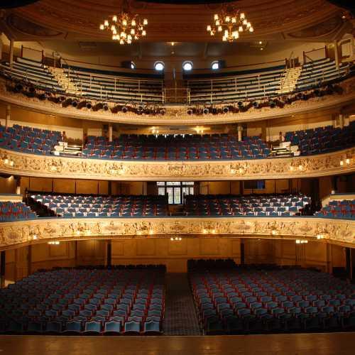 vooraanzicht The Grand Theatre blauwe vaste stoel met houten afwerking model Acanthus