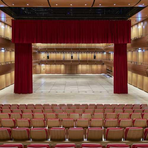 cultureel centrum met telescopische tribune rode stoelen met houten achterkant model Galant